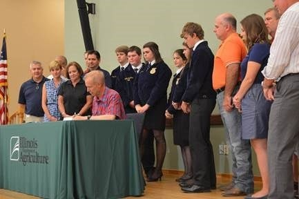 Pittsfield FFA students and Rep Davidsmeyer watch as IL Governor Bruce Rauner signs HB470.