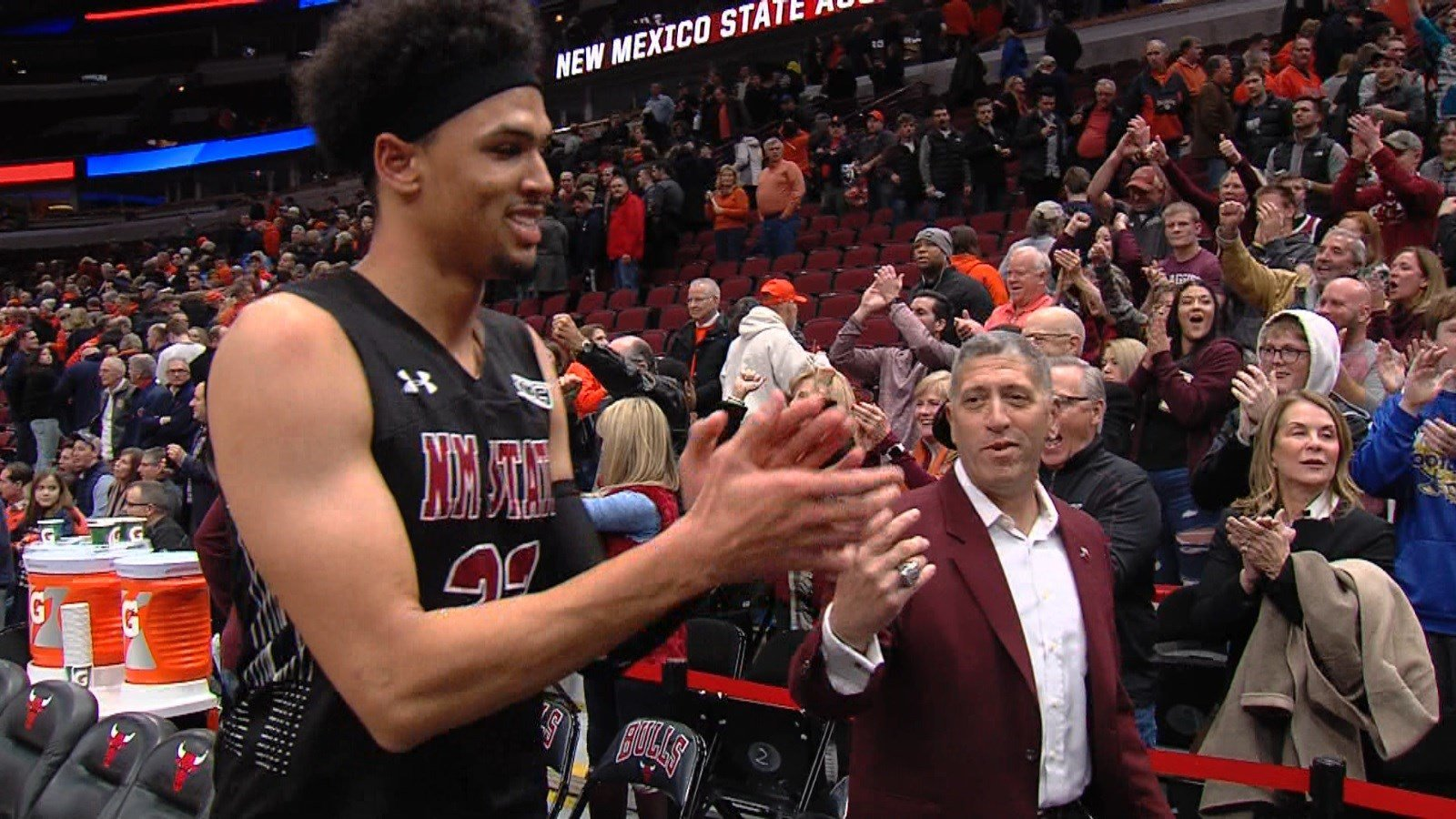 New Mexico State's Eli Chuha celebrates the Aggies' 74-69 win over Illinois with athletic director Mario Moccia and the maroon-clad contingency on hand at the United Center on Saturday in Chicago.