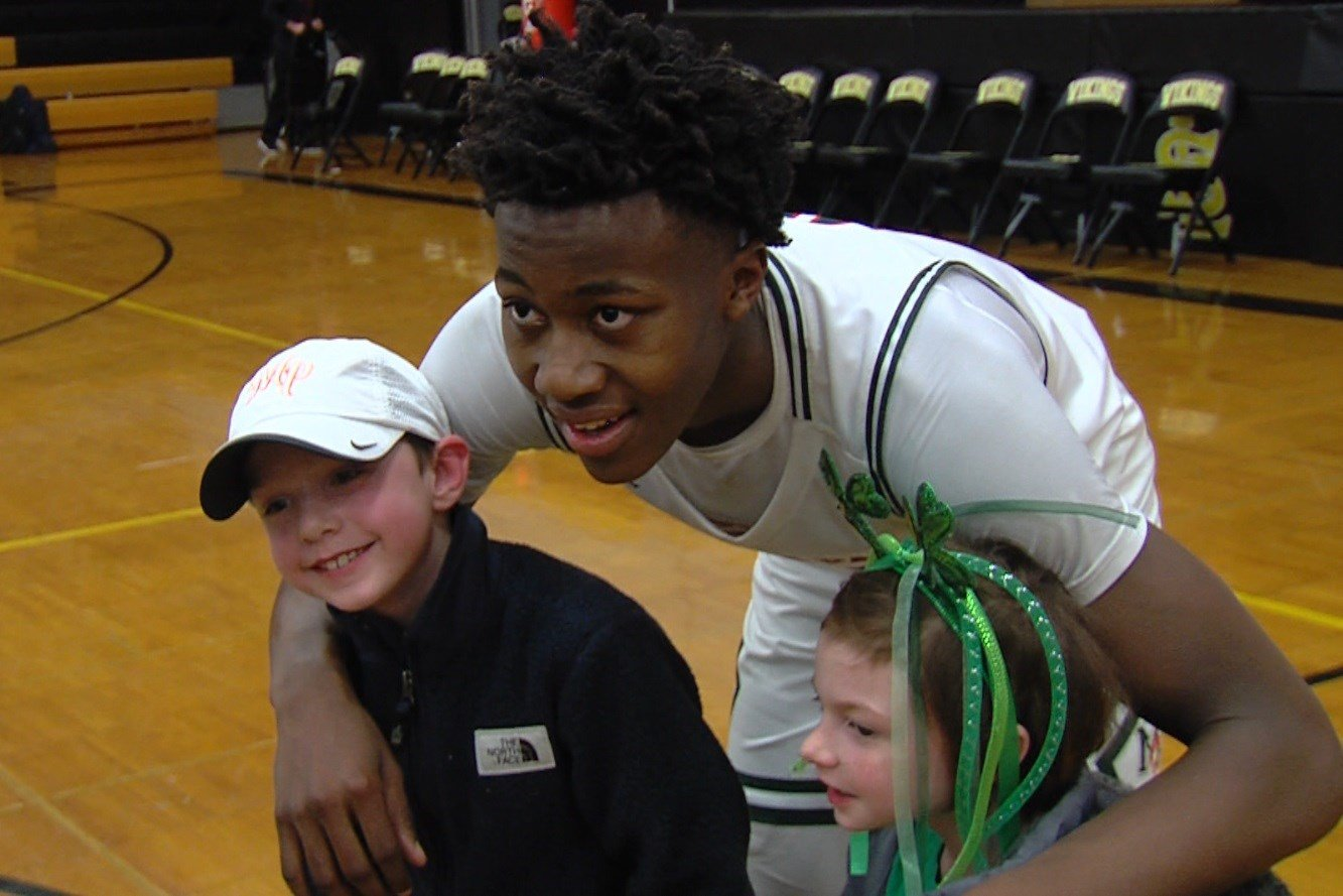 Ayo Dosunmu poses with young fans after contributing a game-high 27 points in No. 1 Morgan Park's 101-71 win over Bogan in the St. Laurence sectional final on Friday in Burbank.