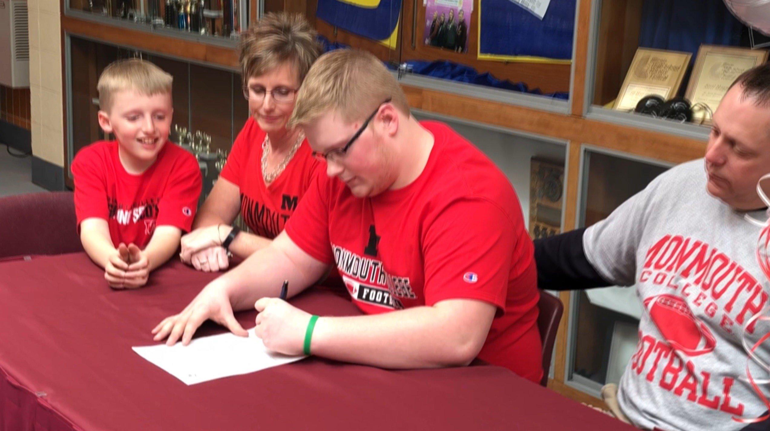 Garrett Hayden signs his letter of intent to play football at Monmouth College. The 260-pounder has a passion for reading books and will major in history.