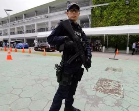 (AP Photo/Wong Maye-E) A police officer guards the entrance to an international media center in Singapore.